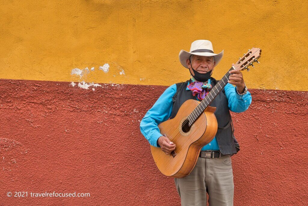 san-miguel-musician-in-front-of-colorful-wall