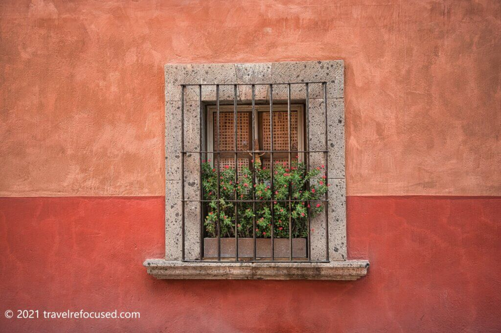 san-miguel-de-allende-window-with-two-toned-wall-and-red-flowers